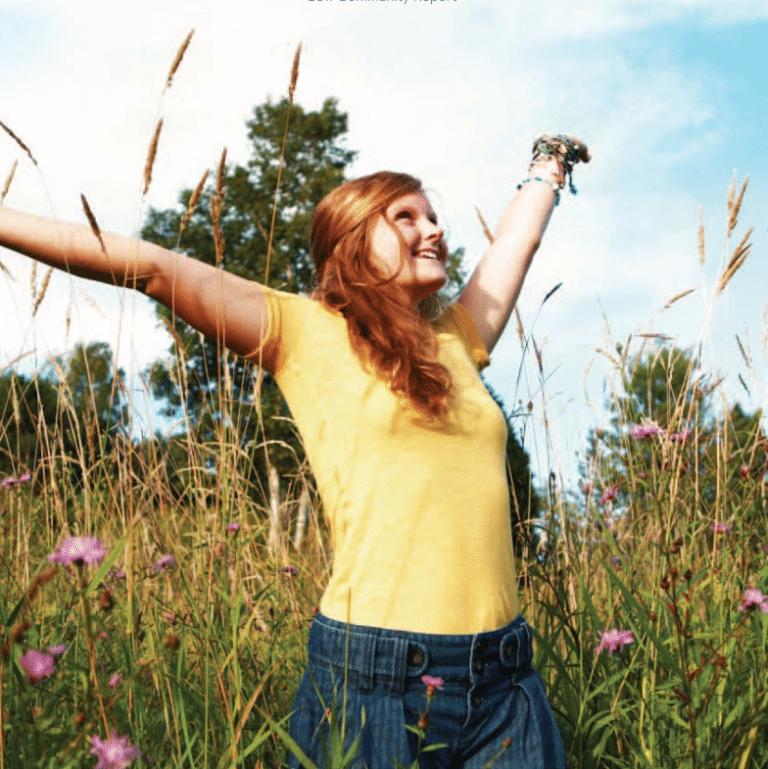 girl in field expressing happiness